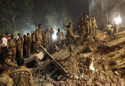 Rescue workers search for survivors under the rubble of a collapsed building in New Delhi November 16, 2010. REUTERS/Adnan Abidi