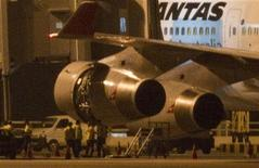 <p>Сотрудники международного аэропорта Чанги осматривают двигатель самолета авиакомпании Qantas, 6 ноября 2010 года. Пассажирский самолет авиакомпании Qantas был вынужден вернуться в Йоханнесбург во вторник вечером после того, как столкновение с птицей повредило один из его реактивных двигателей. REUTERS/Vivek Prakash</p>
