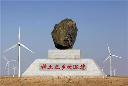 A monument, which reads: ''Home of rare earths welcomes you'', stands in a field of wind turbines near the town of Damao in China's Inner Mongolia Autonomous Region in this October 31, 2010 file photo. REUTERS/David Gray