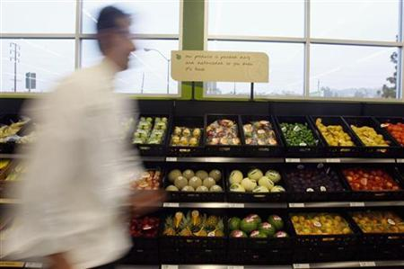 A man walks past packaged fruit and vegetables during the opening ceremony for Tesco's Fresh & Easy Neighborhood supermarket in Los Angeles November 7, 2007. REUTERS/Lucy Nicholson