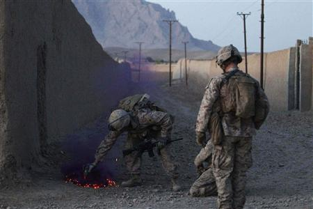 Sgt. Thomas James Brennan of Randolph, Massachusetts (L) from the First Battalion Eighth Marines Alpha Company deploys purple smoke to mark the location of a roadside bomb, or improvised explosive device (IED) discovered during a patrol in the town of Nabuk, Helmand province, October 31, 2010. REUTERS/Finbarr O'Reilly/Files