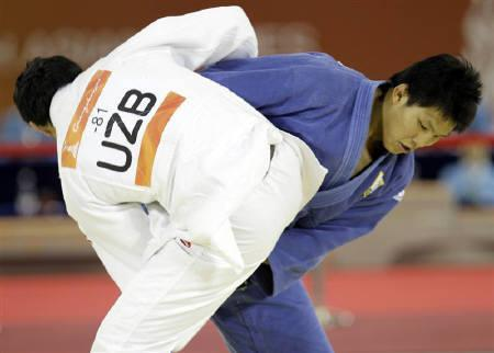 South Korea's Kim Jae Bum (in blue) competes against Uzbekistan's Shokir Muminov in the men's judo -81kg event at the 16th Asian Games in Guangzhou, November 14, 2010.   REUTERS/Jason Lee