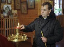 <p>Президент России Дмитрий Медведев в церкви на острове Кунашир, одном из Курильских островов 1 ноября 2010 года. Госдума РФ в пятницу приняла в третьем чтении законопроект, позволяющий Русской православной церкви бесплатно получить около 17.000 объектов недвижимости, которая сейчас принадлежит государству и муниципалитетам. REUTERS/Ria Novosti/Kremlin/Mikhail Klimentyev</p>