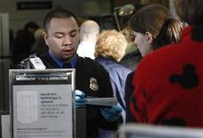<p>A U.S. TSA employee checks passengers' boarding passes and identification at a security chekckpoint at Washington Reagan National Airport.</p>