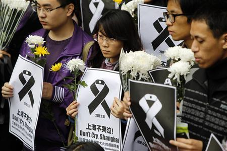 People hold flowers and posters to mourn for the victims of an apartment block blaze at a commemoration ceremony at the entrance of the site in Shanghai November 21, 2010. REUTERS/Aly Song