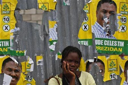 A resident looks on next to presidential election posters of Jude Celestin in Port-au-Prince October 30, 2010. REUTERS/Eduardo Munoz