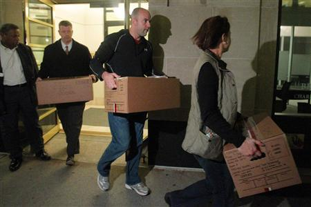 Law enforcement officials carry boxes marked ''Evidence'' out of the building housing Loch Capital Management in Boston, November 22, 2010. REUTERS/Brian Snyder