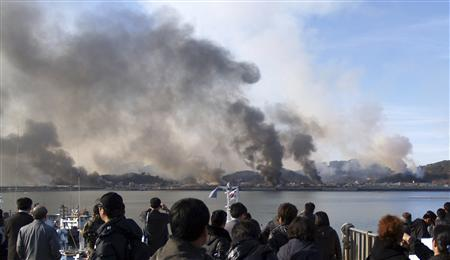 People look as smoke rises from South Korean Yeonpyeong Island after being hit by dozens of artillery shells fired by North Korea November 23, 2010 in this picture taken by a South Korean tourist. REUTERS/Yonhap