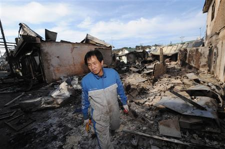 A local resident looks around damaged houses on Yeonpyeong Island November 24, 2010 after the island was hit by artillery shells fired by North Korea. REUTERS/Korea Pool/Newsis