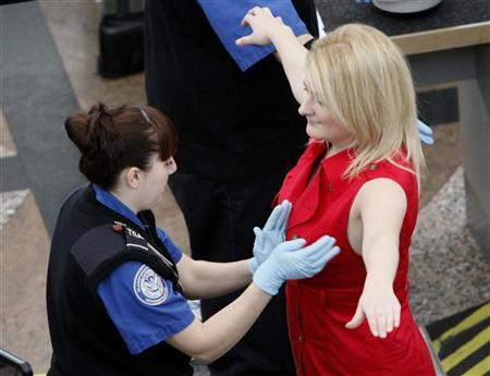 A Transportation Security Agency (TSA) worker runs the back of her hand between a traveller's breasts during a patdown search at Denver International Airport, the day before the Thanksgiving holiday in Denver November 24, 2010. REUTERS/Rick Wilking (UNITED STATES - Tags: TRANSPORT SOCIETY)