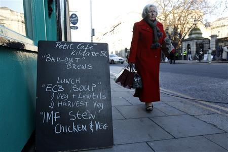 A pedestrian walks past a sign outside a cafe displaying a menu relating to the current economic climate, in Dublin November 23, 2010. REUTERS/Cathal McNaughton