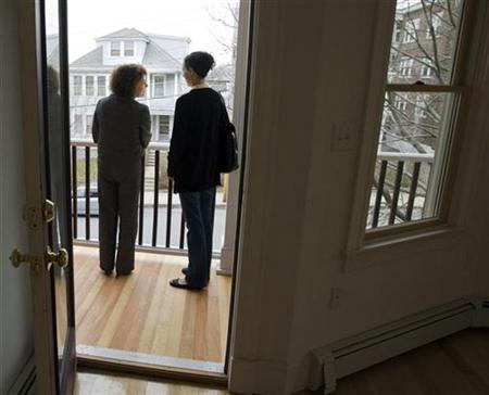 Prospective home buyer Jessica Doctoroff (R) stands on the porch of a condominium for sale with her real estate agent Brenda Bremis in Somerville, Massachusetts April 2, 2009. REUTERS/Brian Snyder