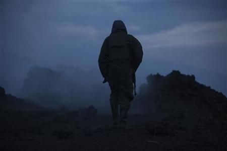 A Congolese soldier and guard for Virunga National Park carries his weapon along the rim of the smouldering crater on Mount Nyiragongo volcano near Goma in eastern Congo, August 30, 2010. REUTERS/Finbarr O'Reilly