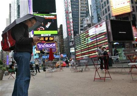 A man looks at his phone in Times Square as a rain storm hits New York, October 1, 2010. REUTERS/Brendan McDermid