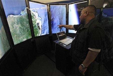 A man looks at screens showing images by Google Earth at the Cancun Messe Convention Center where climate talks are taking place in Cancun, December 1, 2010. REUTERS/Gerardo Garcia