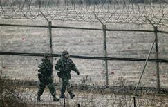 <p>Южнокорейские солдаты патрулируют территорию возле демилитаризованной зоны, разделяющей две Кореи, 2 декабря 2010 года. Южная Корея заявила, что любые повторные атаки со стороны Северной Кореи вызовут с ее стороны ответную бомбардировку при поддержке США. REUTERS/Jo Yong-Hak</p>