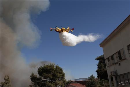 A firefighting aircraft drops water over a forest fire near Yemin Orde Youth Village on Mount Carmel in northern Israel, December 3, 2010. REUTERS/Baz Ratner
