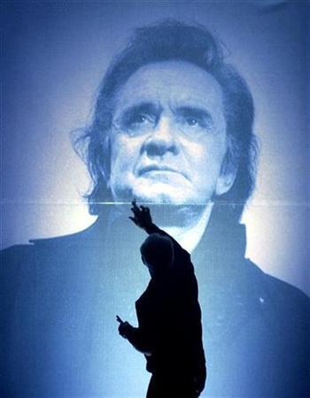A stage hand at the Ryman Auditorium puts the final touchs on a large photo of the late country music legend Johnny Cash, before the Cash tribute concert in Nashville, Tennessee, late November 10, 2003. REUTERS/John Sommers II