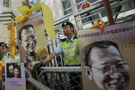 Protesters hang postcards of jailed Chinese Nobel Peace Prize laureate Liu Xiaobo with yellow ribbon outside the Chinese liaison office during a protest to urge the release of Liu in Hong Kong December 5, 2010. REUTERS/Tyrone Siu