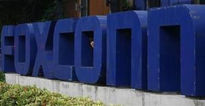 <p>Foto de archivo de un empleado observando desde el cartel de la firma Foxconn en Longhua, China, mayo 27 2010. La compañía electrónica china Foxconn Electronics, uno de las principales fabricantes de los productos de Apple, tiene previsto comenzar a enviar el nuevo modelo del computador iPad, conocido como iPad 2, para fines de febrero, publicó el martes la página de internet DigiTimes. REUTERS/Bobby Yip</p>