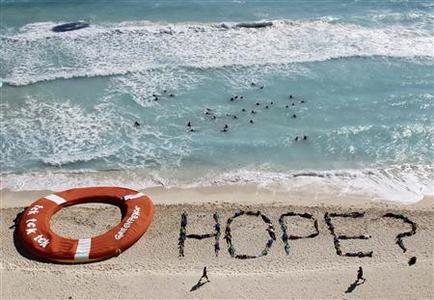Activists of Environment Greenpeace perform next to a giant life ring, during talks on climate change, in Cancun beach December 10, 2010. REUTERS/Henry Romero