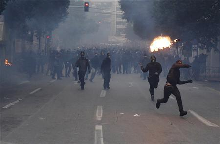Protesters throw petrol bombs at policemen during clashes in Athens December 15, 2010. REUTERS/John Kolesidis
