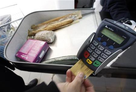 A shopper pays with his credit card in a supermarket in Nice southern France, February 25, 2008. REUTERS/Eric Gaillard