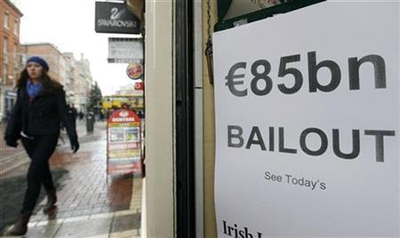 A woman walks along Grafton Street past a newspaper flyer reporting on the government bailout Dublin November 29, 2010. REUTERS/Cathal McNaughton