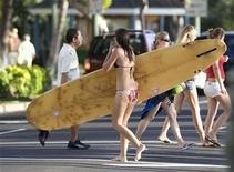 <p>Серфингистка проходит по улице в Гонолулу 2 января 2010 года. Гавайи - это рай на карте США, цепь островов с поражающими взор горами и чарующими пляжами. REUTERS/Larry Downing</p>