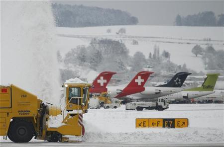 Workers use a blower to remove snow from the tarmac of Zurich airport in Kloten after the region was hit by strong snow falls, December 17, 2010. REUTERS/Christian Hartmann (SWITZERLAND - Tags: ENVIRONMENT TRANSPORT)