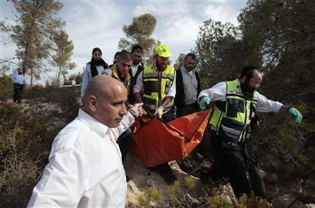Israeli emergency personnel carry the body of U.S. tourist Christine Logan, discovered in a wooded area near the village of Matta, south of Jerusalem December 19, 2010. Logan was stabbed to death and another woman wounded while hiking in Israel, police said on Sunday. ''We are examining whether this is a nationalistic stabbing, but other leads are being examined as well,'' police spokesman Micky Rosenfeld said, using Israel's term for an attack by Palestinian militants. REUTERS/Baz Ratner