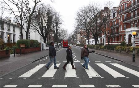 Tourists pose for a photograph on the pedestrian crossing at Abbey Road in St. Johns Wood, north London December 22, 2010. REUTERS/Andrew Winning