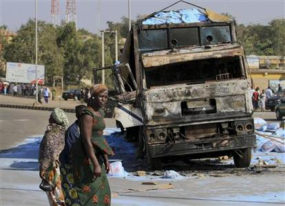 People walk past the wreckage of a burnt truck along a road in Nigeria's central city of Jos December 25, 2010. REUTERS/Afolabi Sotunde