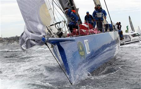 Crew members of supermaxi yacht Wild Thing gesture before they collide with a media boat at the start of the annual Sydney to Hobart yacht race in Sydney Harbour December 26, 2010. REUTERS/Daniel Munoz
