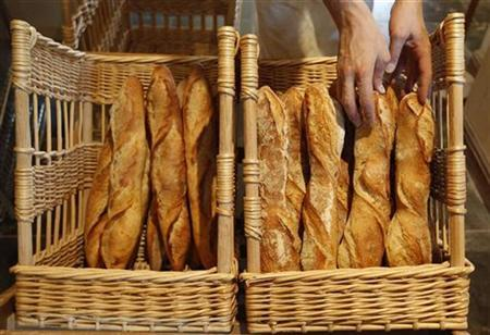 A French baker places freshly-baked 'baguettes', the traditional French bread, in wicker baskets in his shop in Strasbourg eastern France in this August 6, 2010 file photo. REUTERS/Vincent Kessler