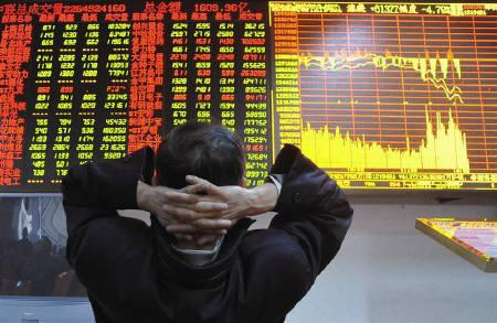 An investor sits in front of an electronic board displaying stock information at a brokerage house in Xiangfan, Hubei province, November 16, 2010. REUTERS/Stringer Shanghai/Files