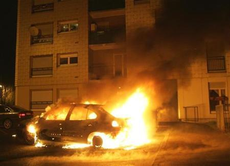 Flames engulf a burning car outside council housing flats on New Year's Eve in Strasbourg's western suburb of Hautepierre December 31, 2008. REUTERS/Jean Marc Loos