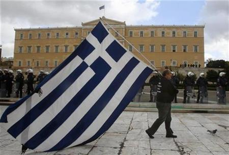 A striker parades with a huge Greek flag in front of riot police guarding the parliament during a demonstration in central Athens December 22, 2010. REUTERS/Yannis Behrakis