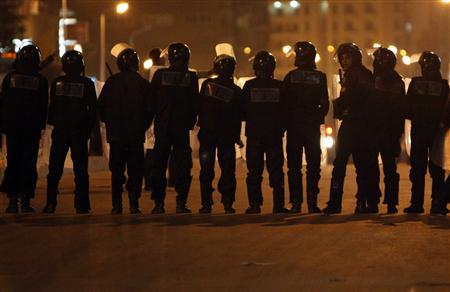 Riot police stand across a street as Coptic Orthodox demonstrators throw stones at them while demanding to enter the Coptic Orthodox Church of the Two Saints where Saturday's bomb attacks had taken place in Alexandria January 2, 2011. REUTERS/Asmaa Waguih