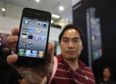 Boonchu Juramongkol, 34, shows his new iPhone 4 at a shop in Bangkok September 24, 2010. REUTERS/Chaiwat Subprasom
