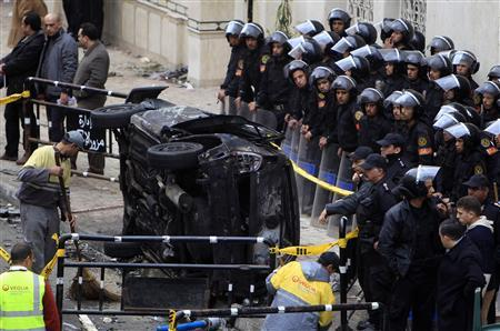 Egyptian riot police look on as cleaners sweep the site of a car bombing in front of a mosque in Alexandria, 230 km (140 miles) north of Cairo January 1, 2011. REUTERS/Amr Abdallah Dalsh