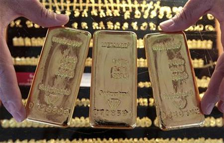 A shopkeeper shows gold bars after buying them from a customer in Bangkok's Chinatown October 14, 2010. REUTERS/Sukree Sukplang