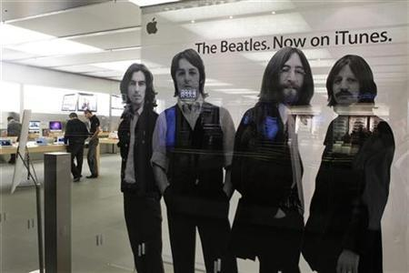 Customers browse products near a picture of The Beatles at the Apple store at the Glendale Galleria in Glendale, California December 8, 2010. To match Reuters Life! APPLE/STORE REUTERS/Fred Prouser