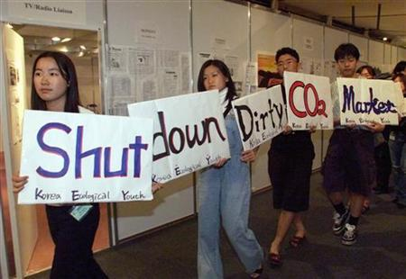 Members of the Korean Ecological Youth group protest against developed countries' emissions of greenhouse gases by walking with a sign saying ''Shut Down Dirty CO2 Market''. Picture taken November 13, 1998. REUTERS/Rickey Rogers