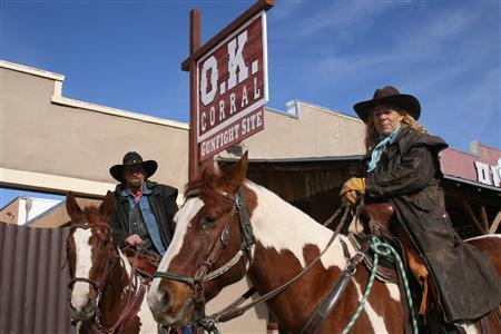 Cowboys Chris Wheeland and Cecilia Barron pose on horseback outside the OK Corral site in Tombstone, Arizona, January 9, 2010. REUTERS/Tim Gaynor