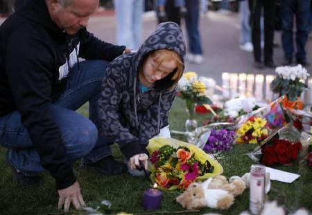 A girl and her father lights a candle at a memorial outside the hospital where victims of yesterday's shootings are recovering in Tucson, Arizona January 9, 2011. REUTERS/Rick Wilking