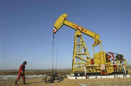 An employee walks past a pump jack at a PetroChina plant on the outskirts of Shenyang, Liaoning province January 13, 2008. REUTERS/Stringer
