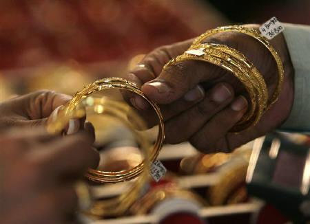 A woman buyer looks at gold bangles at a jewellery shop in Mumbai October 8, 2009. REUTERS/Arko Datta/Files