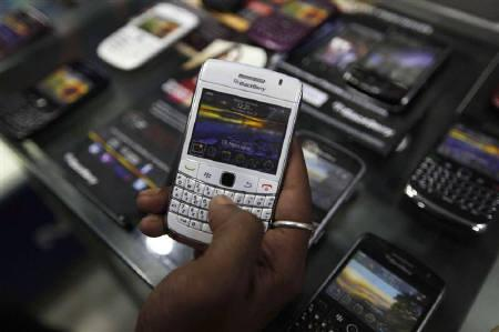 A customer holds a BlackBerry handset inside a shop in Kolkata August 12, 2010. BlackBerry maker Research In Motion said it has given India the means to access its Messenger service and reiterated that no changes could be made to allow monitoring of secure corporate emails. REUTERS/Rupak De Chowdhuri/Files