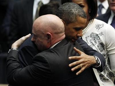 President Barack Obama hugs Congresswoman Gabrielle Gifford's husband, NASA shuttle commander Mark Kelly as first lady Michelle Obama looks on at an event held to support and remember the victims of the mass shooting, at the University of Arizona in Tucson, January 12, 2011. REUTERS/Mike Segar